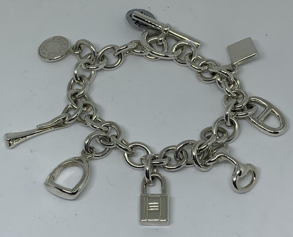 Hermes silver charm bracelet with charms that are from their iconic collections - image 1